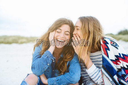 two young female friends whispering on